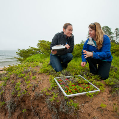 Northland professor engaging with student on Stockton Island over research.