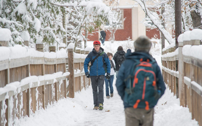 Students walking on bridge in winter.