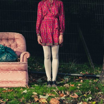 A young woman is standing next to an old armchair outside on the grass