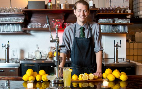 Northland College alumnus Simeon Rossi standing behind bar full of lemons