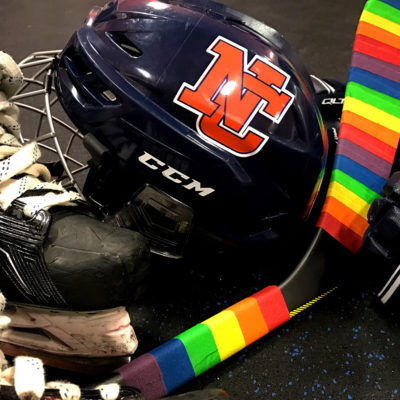 """Hockey gear and hockey stick wrapped with rainbow colored """"Pride"""" tape."""