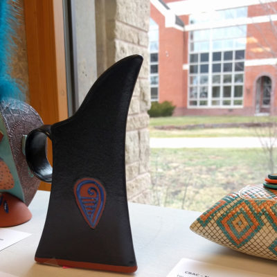 Pottery displayed in Dexter Library with view of Northland College campus in the background.
