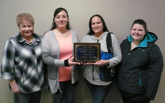 Students stand with award