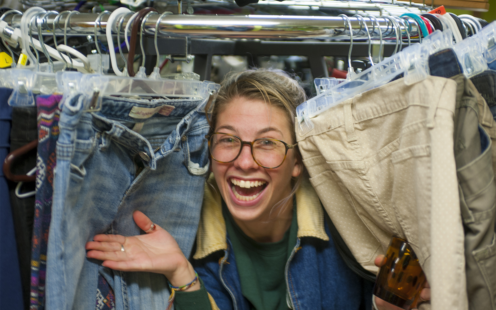 Student in clothes rack in Reuse Room