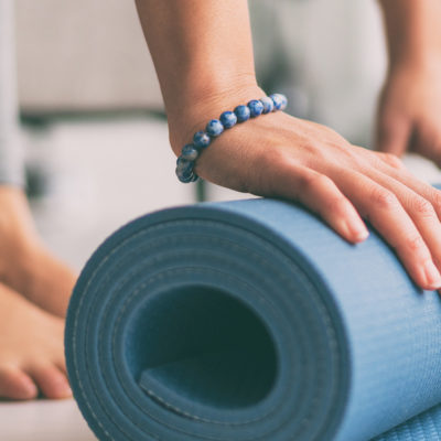 woman rolling yoga mat