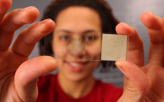 Student holding a microscope slide
